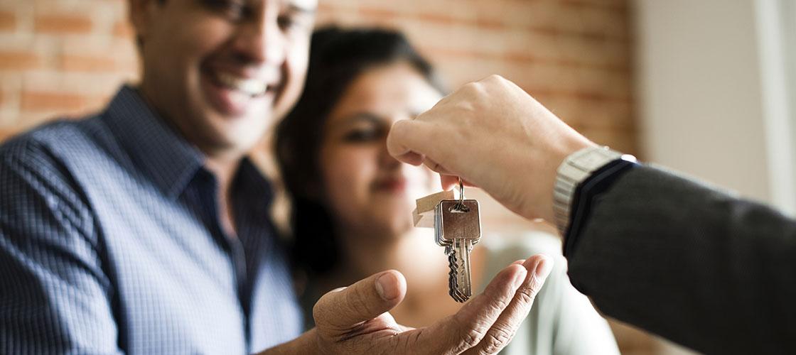 Agent hands couple house keys