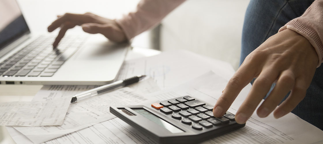 Person crunches refinance numbers on calculator