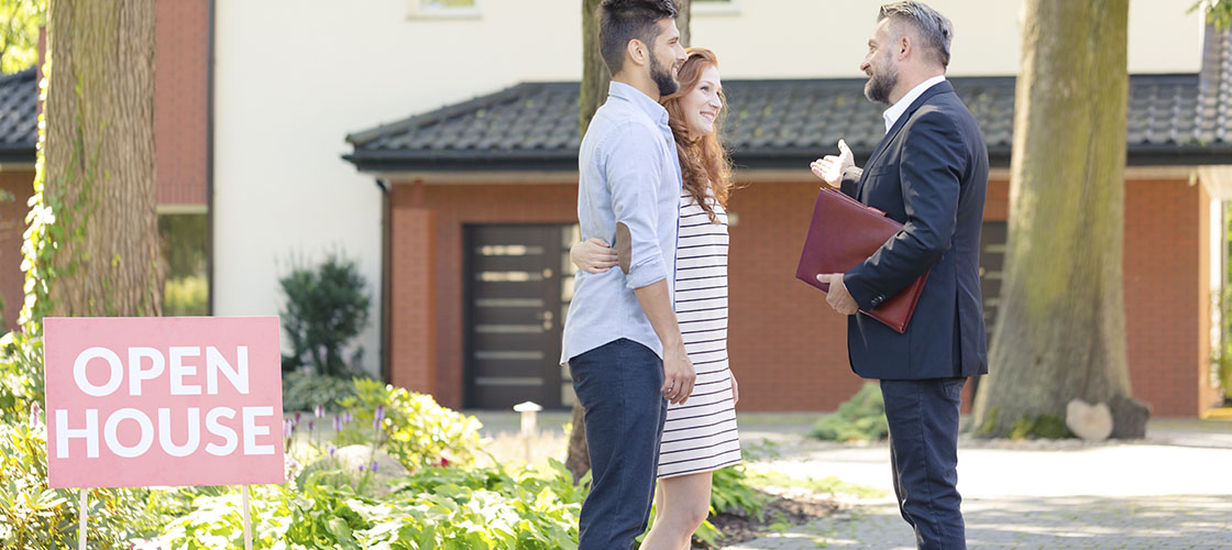 Real estate agent talks to couple at open house