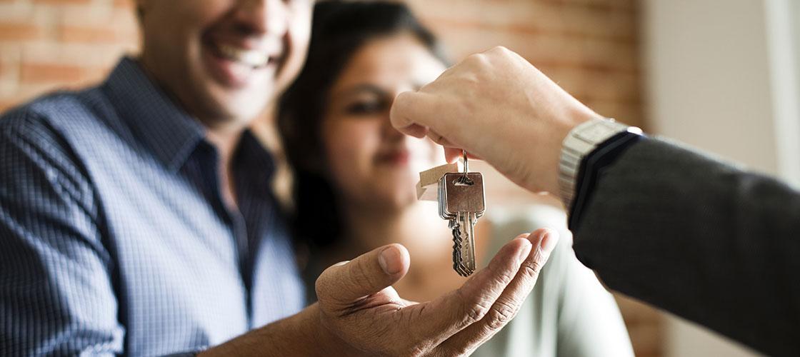 Real estate agent hands couple house keys