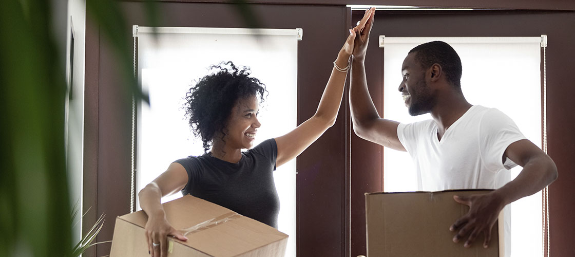 Couple high-fives with moving boxes in new home