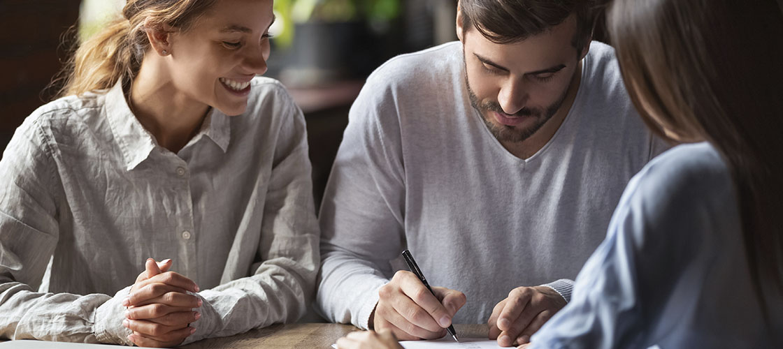 Couple looks over paperwork with local mortgage broker