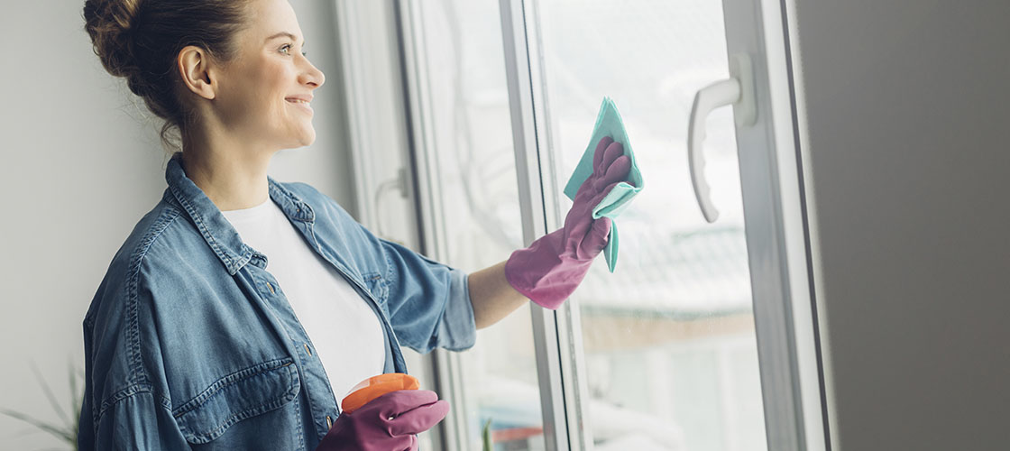 Woman cleaning glass door in new house